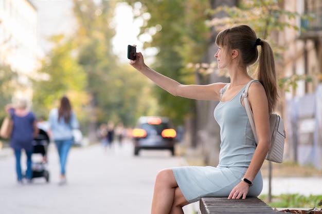 Jonge mooie vrouw die selfie met mobiele telefoon neemt op warme zomerdag, zittend op een straatbankje in de buitenlucht.