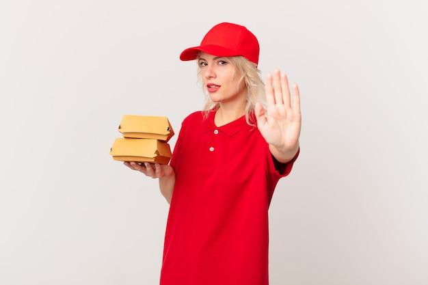 Jonge mooie vrouw die serieus kijkt en open palm toont die een stopgebaar maakt. hamburger bezorgconcept