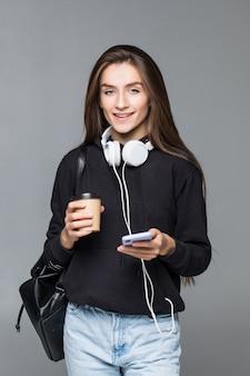 Jonge mooie vrouw die slimme telefoon met behulp van die op grijze muur wordt geïsoleerd