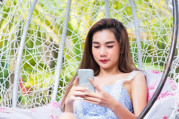 Jonge mooie vrouw die smartphone in schommeling gebruiken