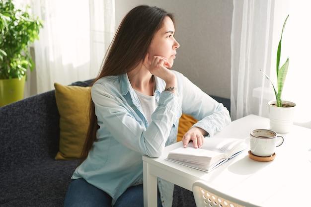 Jonge mooie vrouw die thuis aan tafel zit en een boek leest