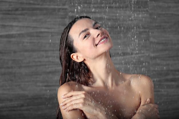 Jonge mooie vrouw die thuis douche neemt