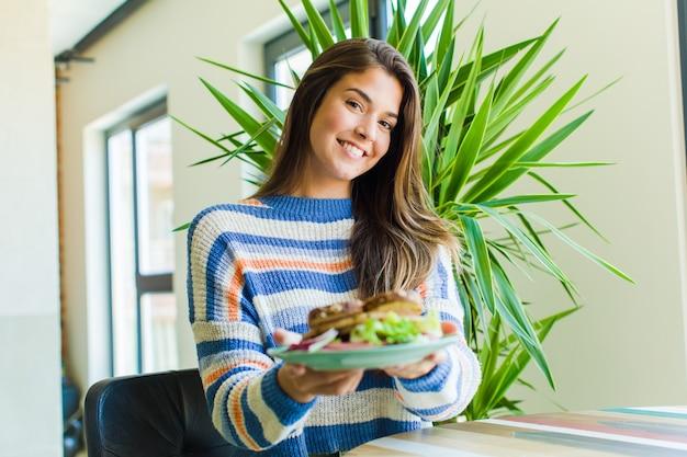 Jonge mooie vrouw die thuis een broodje eet