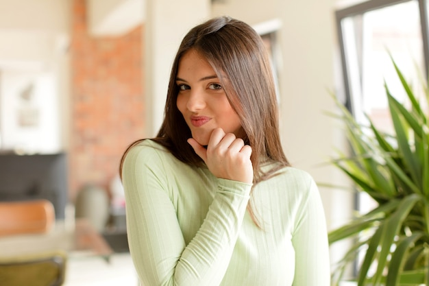 Jonge mooie vrouw die thuis een gebaar maakt