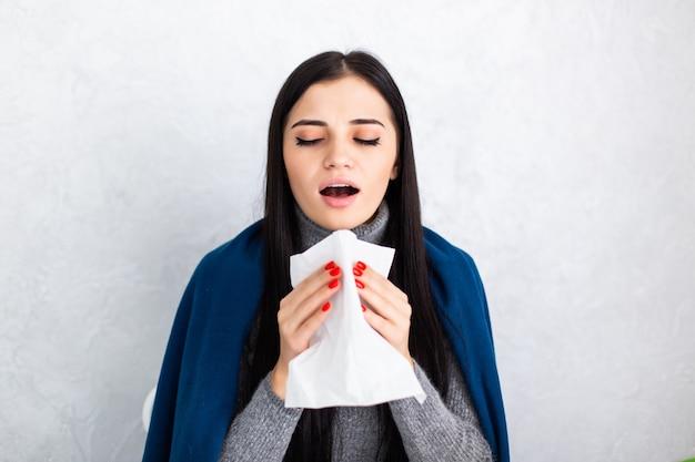 Jonge mooie vrouw die thuis niest
