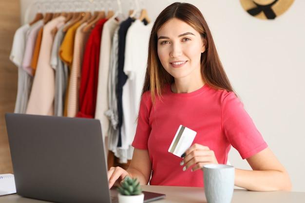 Jonge mooie vrouw die thuis online winkelt