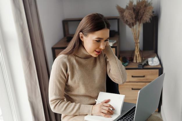 Jonge mooie vrouw die thuis werkt, maakt gebruik van een laptop en mobiele telefoon. vrouw schrijft in bloknota