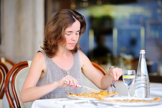 Jonge mooie vrouw die traditionele italiaanse pizza in in openlucht restaurant eet in venetië