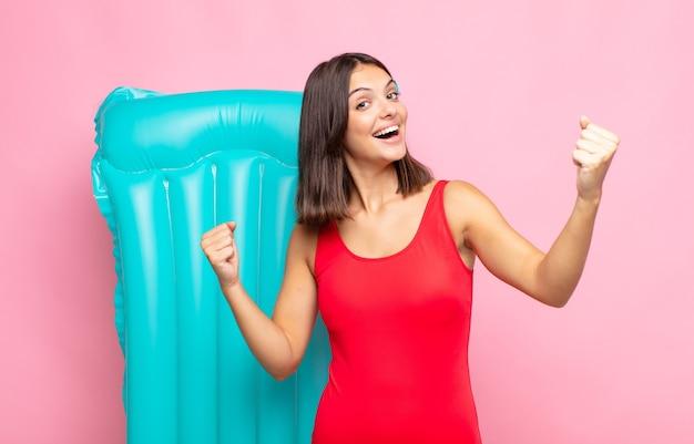 Jonge mooie vrouw die triomfantelijk schreeuwt, eruit ziet als opgewonden, blij en verrast winnaar, viert