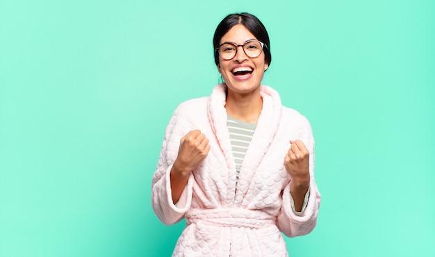 Jonge mooie vrouw die triomfantelijk schreeuwt, lacht en zich blij en opgewonden voelt terwijl ze succes viert