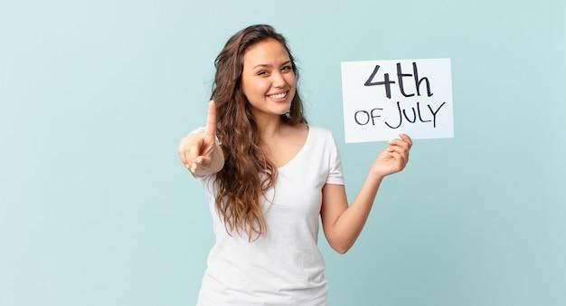 Jonge mooie vrouw die trots en vol vertrouwen glimlacht en het concept van de onafhankelijkheidsdag nummer één maakt