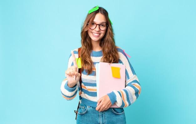 Jonge mooie vrouw die trots en zelfverzekerd glimlacht en nummer één maakt met een tas en boeken vasthoudt