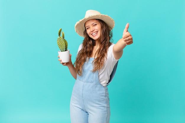 Jonge mooie vrouw die trots is, positief glimlacht met duimen omhoog en een cactus vasthoudt Premium Foto