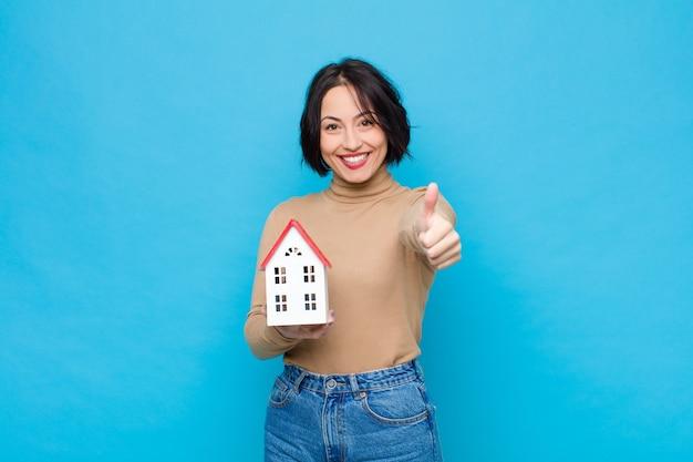 Jonge mooie vrouw die trots, zorgeloos, zelfverzekerd en gelukkig voelt, positief glimlachend met duimen omhoog met een huismodel