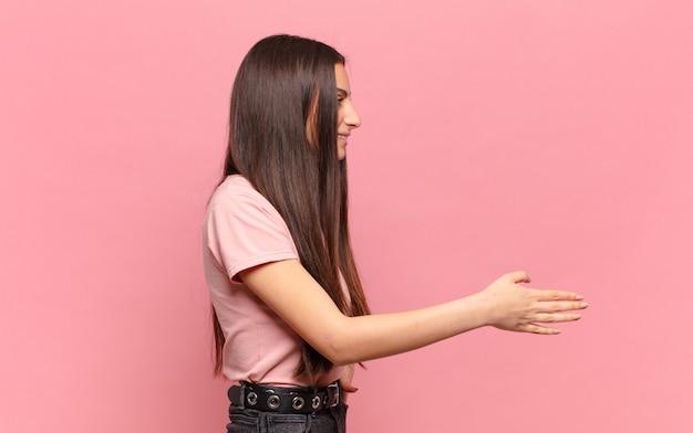 Jonge mooie vrouw die u glimlacht, u begroet en een handschud aanbiedt om een succesvolle overeenkomst, samenwerkingsconcept te sluiten
