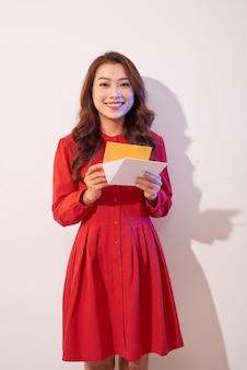 Jonge mooie vrouw die uitnodigingskaart en glimlach kijkt