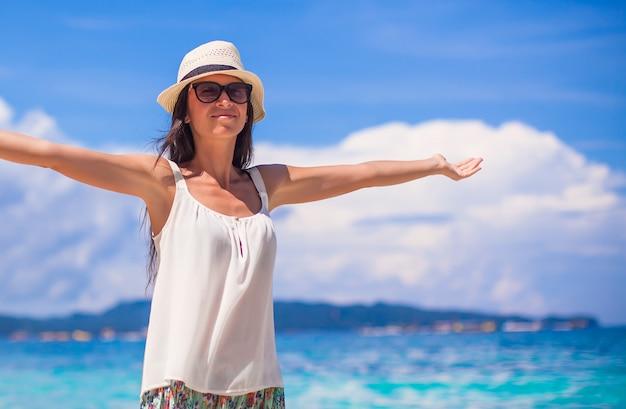 Jonge mooie vrouw die van de vakantie op wit tropisch strand geniet