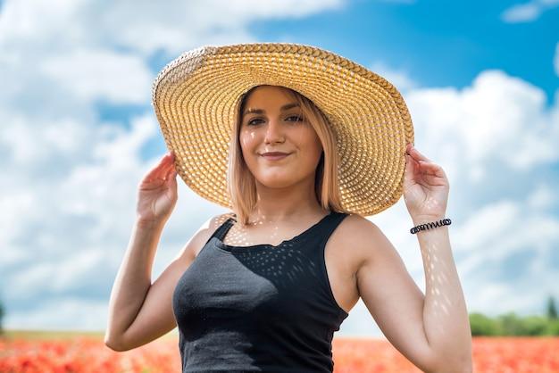 Jonge mooie vrouw die van de zomertijd op het gebied van de papaversbloem geniet