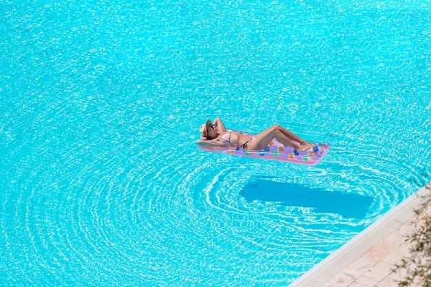 Jonge mooie vrouw die van de zomervakantie in luxe zwembad genieten