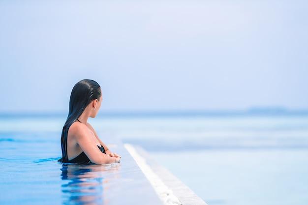 Jonge mooie vrouw die van het luxueuze stille zwembad geniet