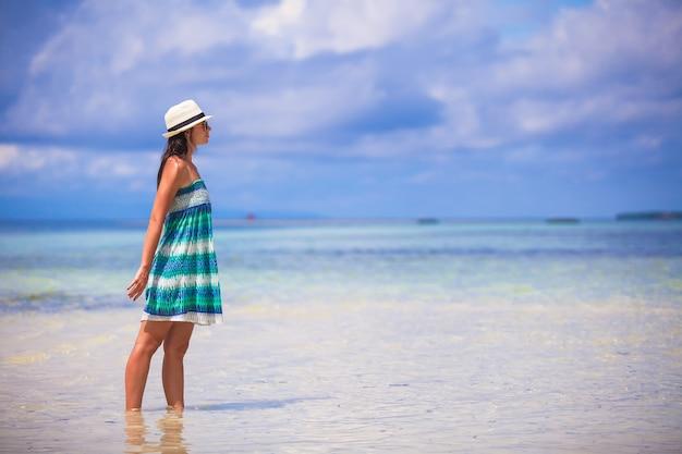 Jonge mooie vrouw die van vakantie op het strand geniet