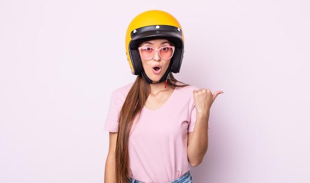 Jonge mooie vrouw die verbaasd in ongeloof kijkt. motorrijder en helm