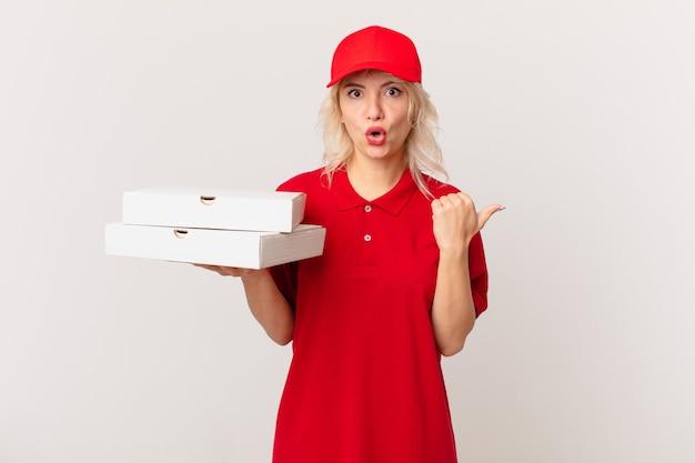 Jonge mooie vrouw die verbaasd in ongeloof kijkt. pizza bezorgconcept