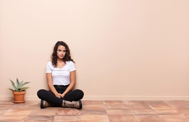 Jonge mooie vrouw die verdrietig en zeurderig is met een ongelukkige blik, huilend met een negatieve en gefrustreerde houding op een terrasvloer zit