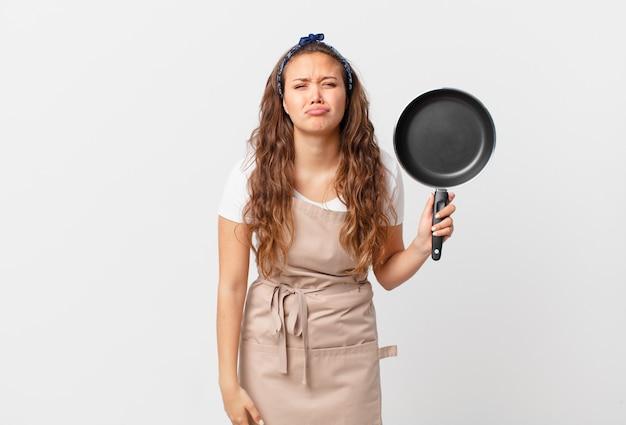 Jonge mooie vrouw die verdrietig en zeurt met een ongelukkige blik en een huilend chef-kokconcept en een pan vasthoudt