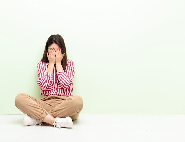 Jonge mooie vrouw die verdrietig, gefrustreerd, zenuwachtig en depressief voelt, gezicht bedekkend met beide handen, huilend zittend op de vloer