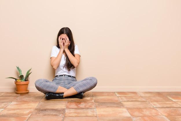 Jonge mooie vrouw die verdrietig, gefrustreerd, zenuwachtig en depressief voelt, gezicht bedekkend met beide handen, huilend zittend op een vloer