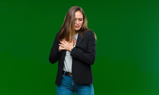 Jonge mooie vrouw die verdrietig, gekwetst en diepbedroefd kijkt, beide handen dicht bij het hart houdt, huilt en zich depressief voelt tegen een groene muur