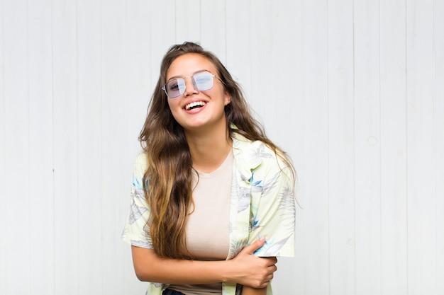 Jonge mooie vrouw die verlegen en opgewekt lacht, met een vriendelijke en positieve maar onzekere houding
