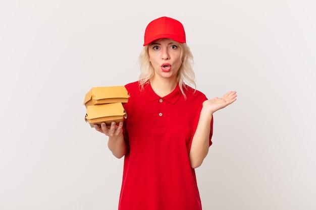 Jonge mooie vrouw die verrast en geschokt kijkt, met open mond terwijl ze een object vasthoudt. hamburger bezorgconcept