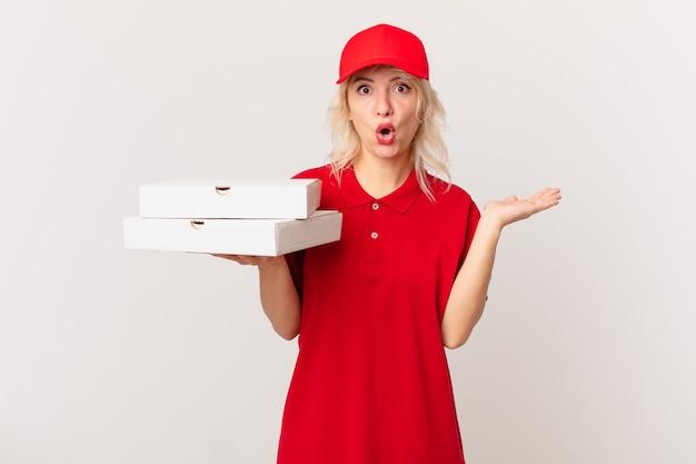 Jonge mooie vrouw die verrast en geschokt kijkt, met open mond terwijl ze een object vasthoudt. pizza bezorgen