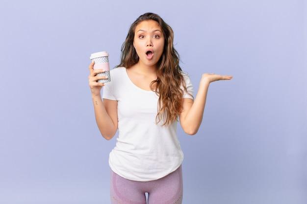 Jonge mooie vrouw die verrast en geschokt kijkt, met open mond terwijl ze een voorwerp vasthoudt en een kopje koffie vasthoudt