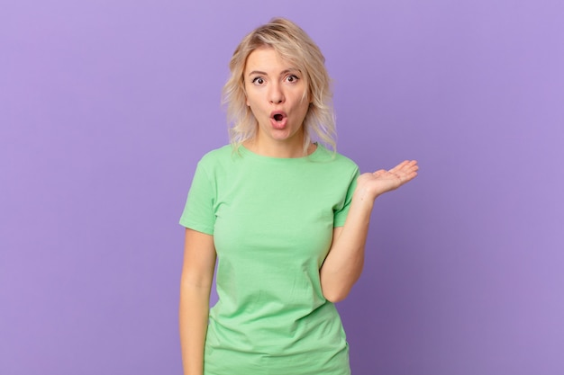 Jonge mooie vrouw die verrast en geschokt kijkt, met open mond terwijl ze een voorwerp vasthoudt