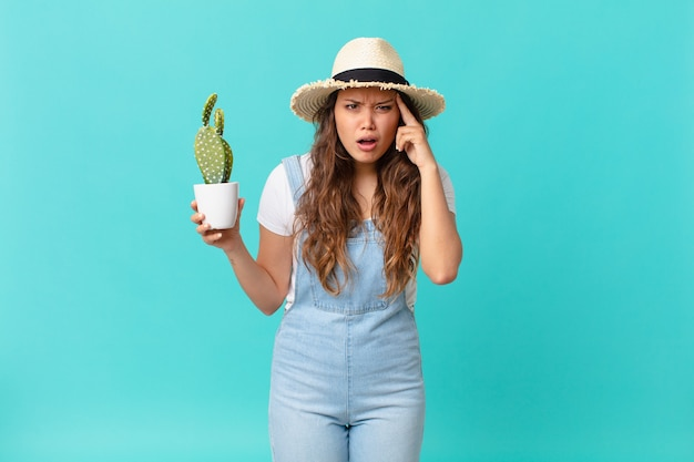 Jonge mooie vrouw die verrast kijkt, een nieuwe gedachte, idee of concept realiseert en een cactus vasthoudt