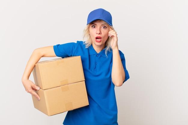 Jonge mooie vrouw die verrast kijkt, een nieuwe gedachte, idee of concept realiseert. pakket leveren concept