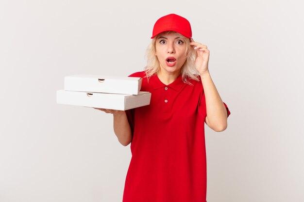 Jonge mooie vrouw die verrast kijkt, een nieuwe gedachte, idee of concept realiseert. pizza bezorgconcept