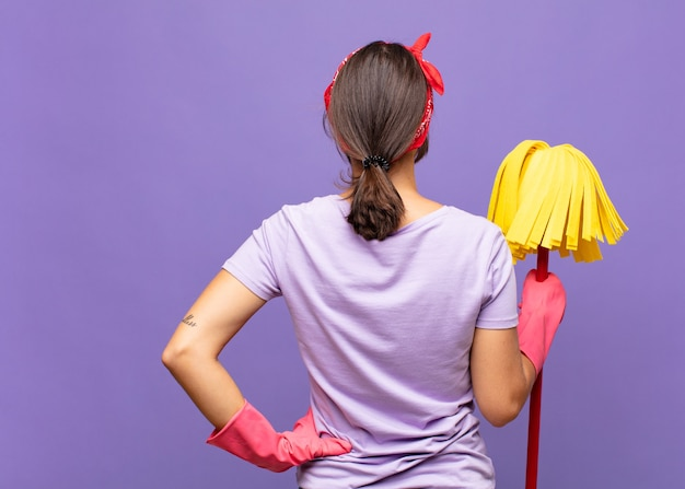 Jonge mooie vrouw die verward of vol of twijfels en vragen voelt, zich afvraagt, met de handen op de heupen, zicht naar achteren