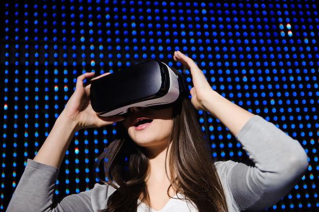 Jonge mooie vrouw die virtuele werkelijkheidsglazen ervaart