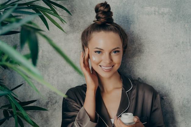 Jonge mooie vrouw die vochtinbrengende crème op haar gezicht aanbrengt, glimlachend op camera en zachtjes aanraken van een gezonde huid, geïsoleerd over betonnen muur thuis. cosmetische behandelingen tegen veroudering en huidverzorgingsconcept
