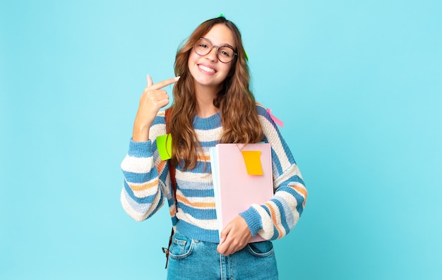 Jonge mooie vrouw die vol vertrouwen glimlacht, wijst naar een brede glimlach met een tas en boeken vasthoudt