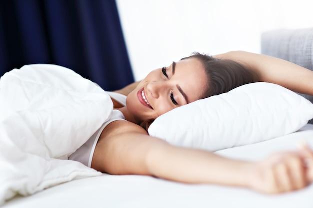 Jonge mooie vrouw die volledig uitgerust wakker wordt in haar bed