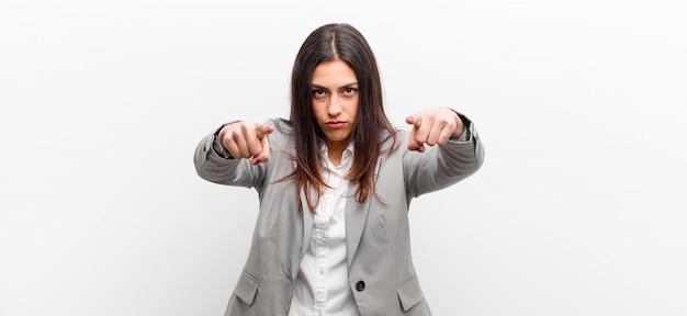 Jonge mooie vrouw die vooruit op camera met zowel vingers als boze uitdrukking richt, die u vertelt om uw plicht te doen die tegen witte muur wordt geïsoleerd