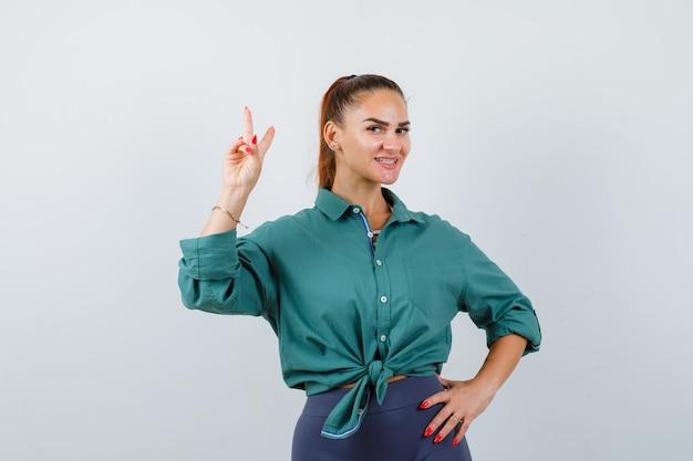 Jonge mooie vrouw die vredesgebaar in groen shirt toont en er positief uitziet, vooraanzicht.