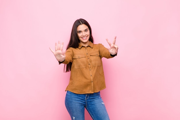 Jonge mooie vrouw die vriendelijk glimlacht en kijkt, nummer acht of achtste met vooruit hand toont, aftellend tegen roze muur