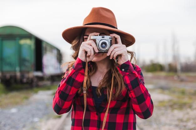 Jonge mooie vrouw die vrijetijdskleding en een hipsterhoed draagt die een beeld met een uitstekende camera nemen