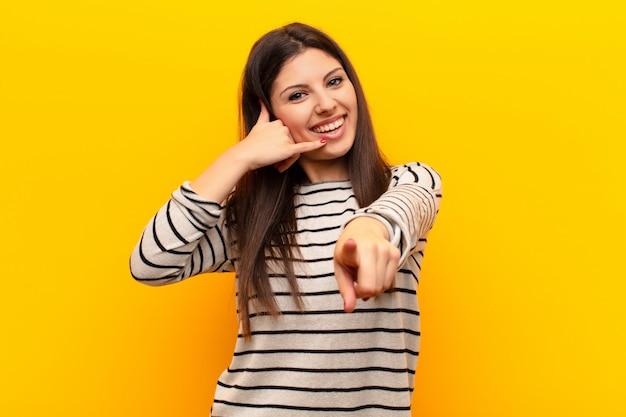 Jonge mooie vrouw die vrolijk glimlachen en aan camera richten terwijl het telefoneren van u later gebaar, sprekend op telefoon tegen gele muur